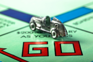 Monopoly board with car on go